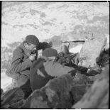 Un binôme FM du 86e BCA est posté dans un amas rocheux, les deux chasseurs sont photographiés de dos, ils servent un FM M24/29.