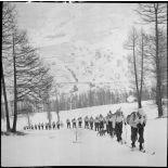 Une section d'éclaireurs-skieurs en mission de reconnaissance gravit une pente enneigée.