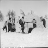 Des éclaireurs-skieurs s'affairent autour d'un igloo.