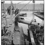 Chargement de torpilles, à l'aide d'un palan, dans les tubes lance-torpilles d'une tourelle orientable d'un sous-marin, à quai dans un port.