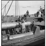 Chargement, à l'aide d'un palan, de torpilles dans les tubes lance-torpilles d'une tourelle orientable d'un sous-marin, à quai dans un port.