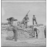 Des marins, appartenant à la 4e batterie mobile de défense antiaérienne de la Marine, effectuent des travaux de terrassement et empilent des sacs de sable afin de consolider la protection autour d'un canon antiaérien de 90 mm.