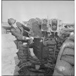 Un lieutenant de vaisseau, appartenant à la 4e batterie mobile de défense antiaérienne de la Marine, s'installe sur un télépointeur (poste optique) qui détermine le pointage des canons de 90 mm CA (contre avions) modèle 1939.